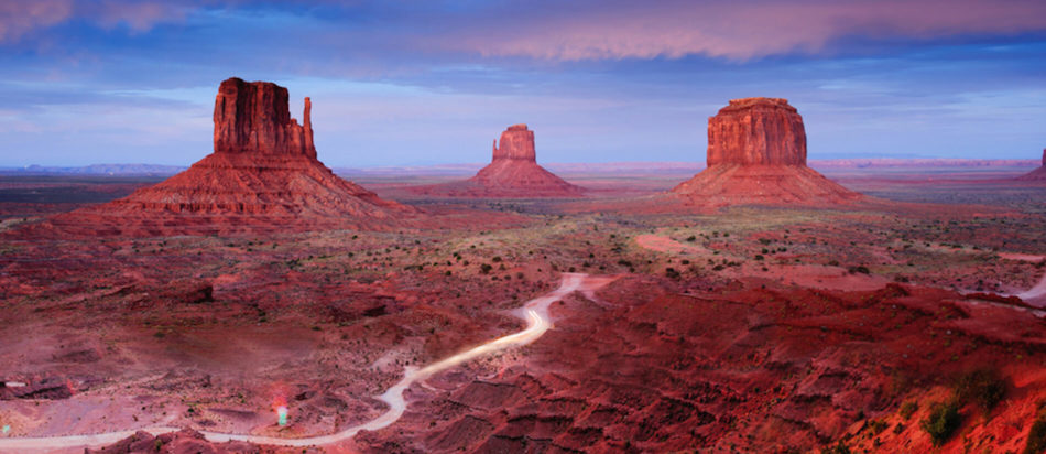 Three Mittens in Monument Valley with road running through