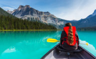 Girl Canoeing on Bright green waters of Emerald Lake, western Canada
